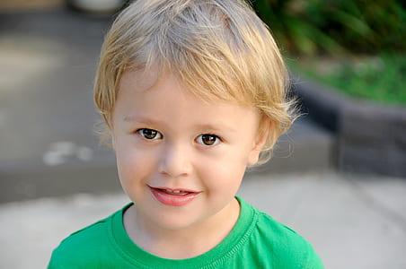 photo of boy wearing green crew-neck shirt
