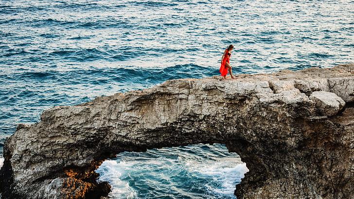 woman walking on gray rock formation