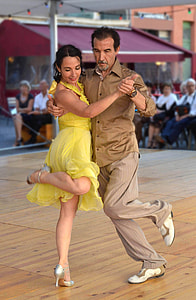 man in brown dress shirt and gray pants dancing with woman in yellow dress