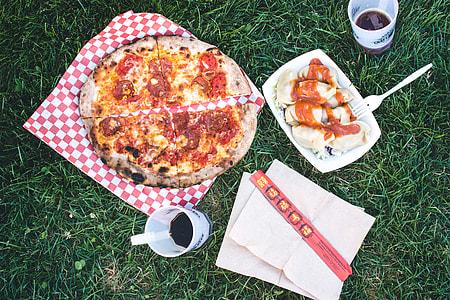 Pizza Salami and Korean dumplings Mandu on a grass