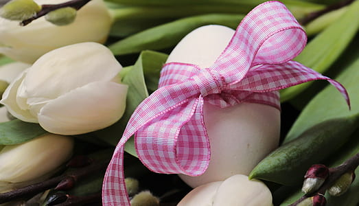 egg with bow on white lily flower