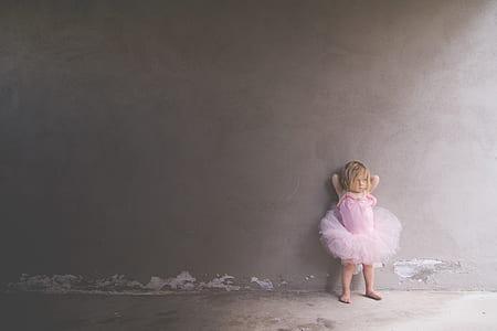 toddler's wearing pink tutu dress leaning on wall