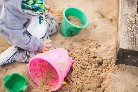 toddler's playing sand on green and pink buckets