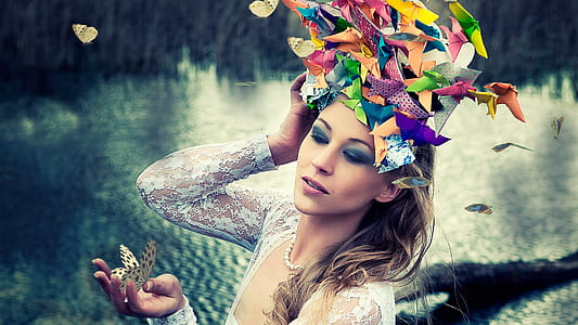 woman with colorful hairdress holding butterfly photo