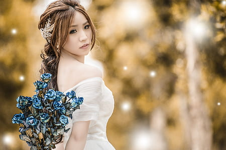 selective focus photo of woman in white off-shoulder dress holds blue petaled flower