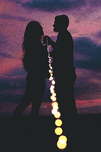 silhouette of woman and man holding string light during nighttime
