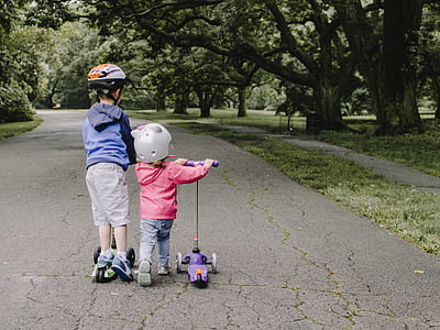two children's playing kick scooters