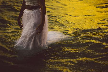 woman wearing white walking on body of water