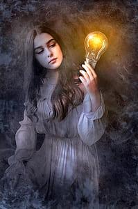 girl in white dress holding light bulb painting