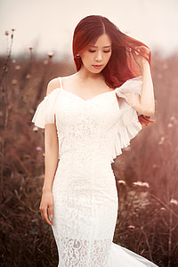 woman in white cold-shoulder dress standing in forest while holding her hair