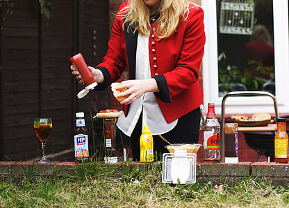 woman in red formal suit in front of bottles