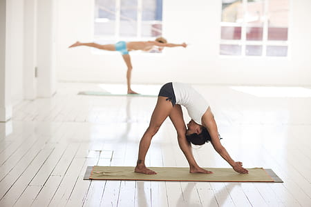 woman in white shirt doing yoga pose on gray mat