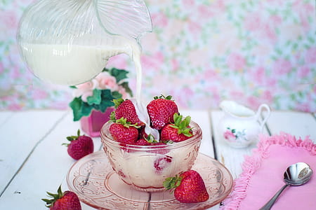 strawberries on cup poured with milk