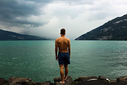 man in black short standing on rock beside lake