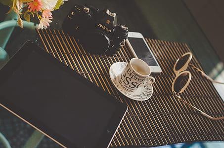 black iPad on table near Nikon DSLR