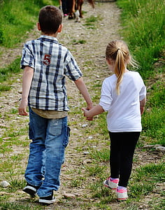 boy and girl holding hands walking on brown pathway
