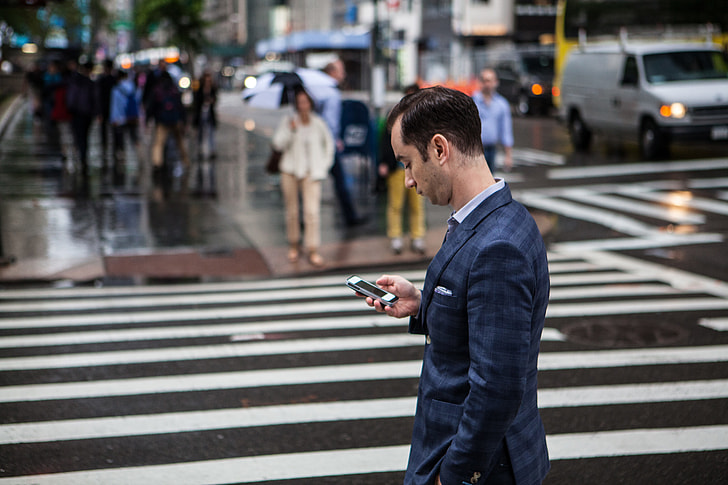 A man checks his mobile iPhone smartphone on a rainy day on the streets of Manhattan, New York City