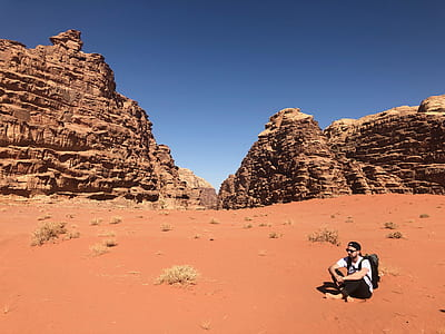 Man Wearing White Shirt and Black Pants Sitting on Soil Behind Rock Formation Mountain