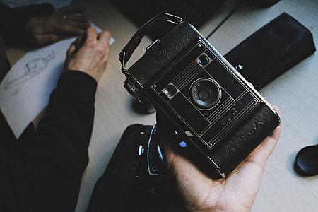 person holding black vintage camera