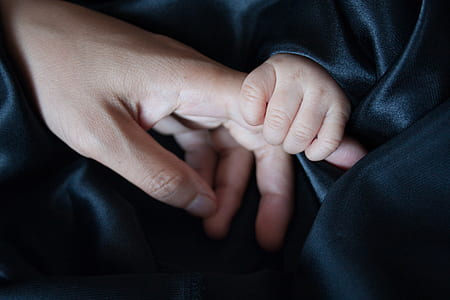 baby holding person's finger