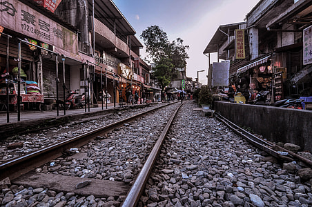 train rail surrounded with houses and store buildings