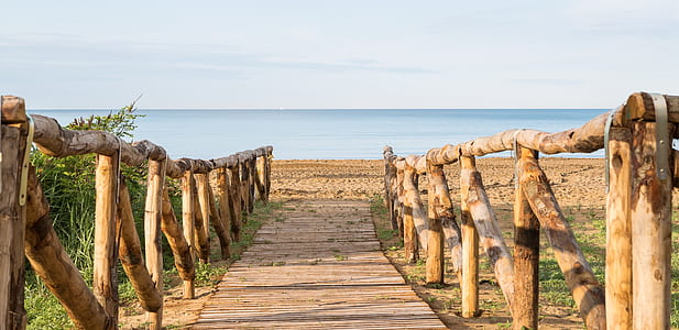 empty wooden pathway leading towards ocean