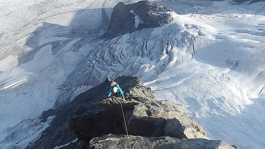 person climbing on mountain at daytime