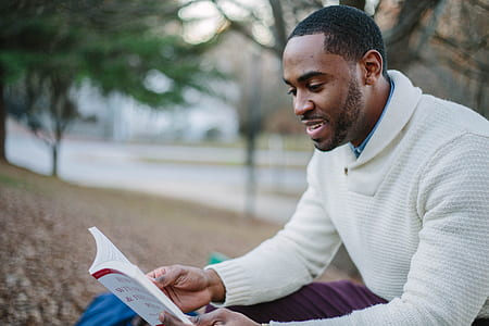 man wears white sweater and reading a book