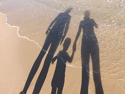 shadow of three person on brown sand