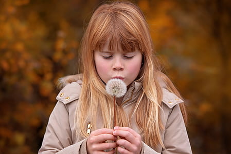 girl in brown coat about to blow dandelion