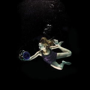 underwater photography of woman holding round alarm clock