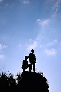 silhouette photo of two boy standing on heels under blue sky