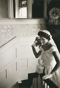 grayscale photo of woman in wedding gown standing beside stair railing
