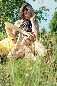 woman lying on lap of another woman sitting on grass wearing sunglasses enjoying the sunlight
