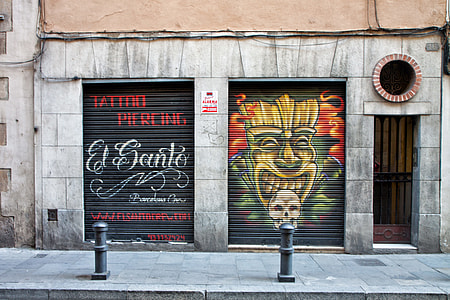 Tattoo and piercing shop with street art in Barcelona, Spain