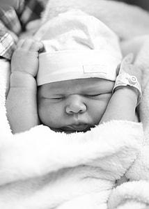 grayscale photo of newborn baby closing her eyes
