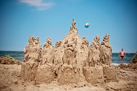grey sand castle near shore during daytime