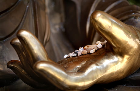 assorted stones on hand of statue