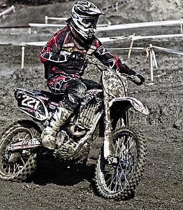 man with red and black racing suit riding on black and white dirt bike motocross during daytime