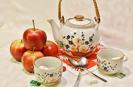 four red apples near white and multicolored ceramic teapot near two white ceramic teacups and two spoons