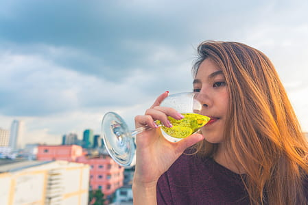 Woman in Purple Top Drinking on Clear Wine Glass