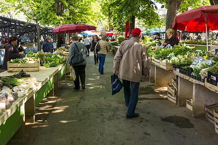 people walking on pathway in between vegetable stands