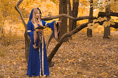 woman dressed as a wizard in the forest casting a spell