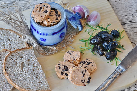 sliced bread on chopping board besides jar, onion, and berries