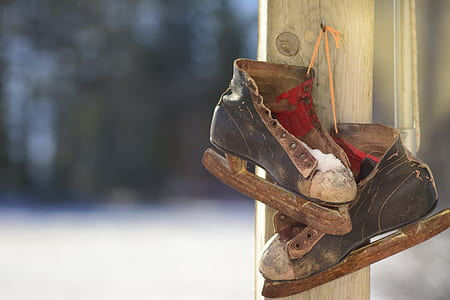 old black-and-brown ice skates hanging on gray wooden post during daytime