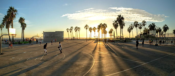 panorama shot of people playing basketball during golden hour