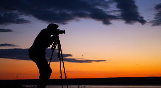 slihouette photo of man using telescope during sunset