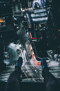 photo of person's leg with view of city during night time