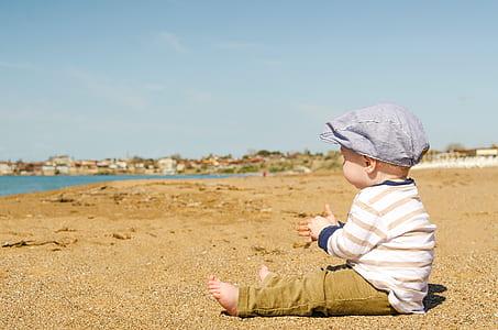 baby sitting on sand facing seashore