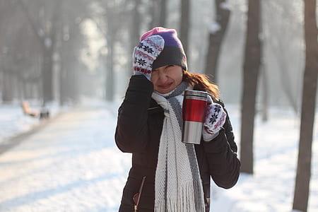 woman holding mug ans wearing hat